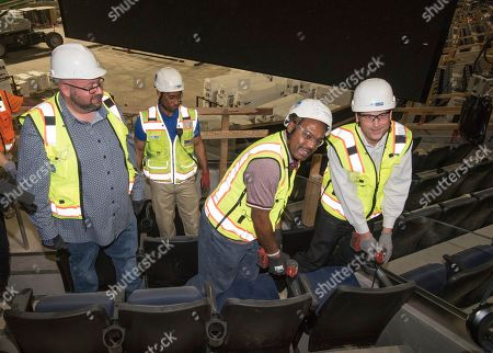 Justin Burleigh, Chief Product Officer for Ticketmaster North America, left, looks on as Tim Hardaway, Golden State Warriors Legend, center, and Mark Carpenter, a 30-Year Warriors Season Ticket Holder, drill in the final seat to celebrate the New Chase Center's Long-Term Official Ticketing and Technology Partnership with Ticketmaster on in San Francisco