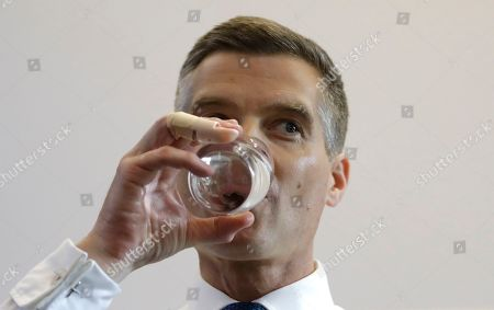 Conservative Party leadership contender Mark Harper takes a drink as he launches his campaign, in London, . The Conservatives are holding an election to replace Prime Minister Theresa May, who resigned as party leader last week after failing to lead Britain out of the European Union on schedule