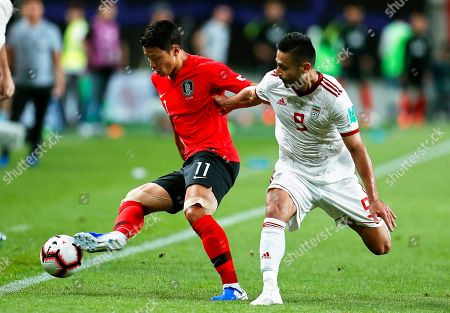Hwang Hee-chan (L) of South Korea in action against Omid Ebrahimi (R) of Iran during the International Friendly soccer match between South Korea and Iran at the Seoul World Cup Stadium in Seoul, South Korea, 11 June 2019.