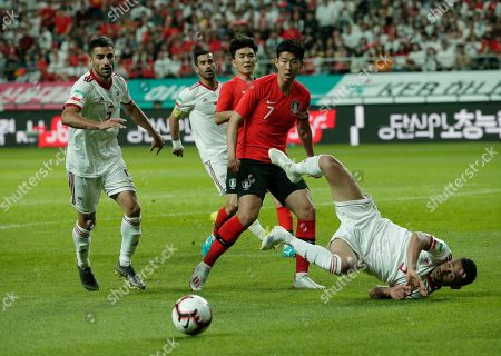 Son Heung-min, Omid Ebrahimi. South Korea's Son Heung-min, second from right, watches after clashing with Omid Ebrahimi, during their friendly soccer match in Seoul, South Korea