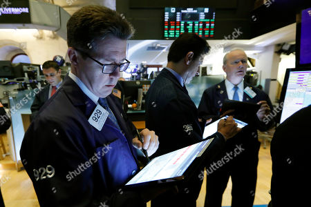 James Matthews, left, works with fellow traders on the floor of the New York Stock Exchange, . Stocks are rising early Tuesday as Wall Street continues to thrive in June