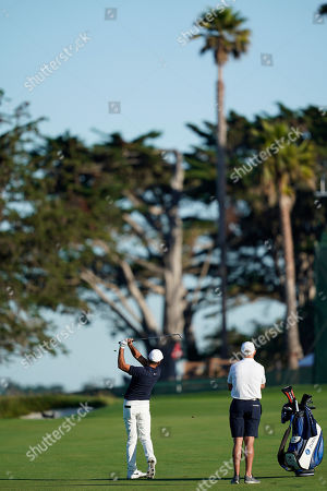 Jason Day, left, of Australia, hits from the fairway as caddie Steve Williams watches on the 13th hole during a practice round for the U.S. Open Championship golf tournament, in Pebble Beach, Calif