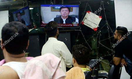 People watch a televised speech of Pakistan's Prime Minister Imran Khan, in Karachi, Pakistan, . Khan vowed to ensure that former President Asif Ali Zardari and ex-Premier Nawaz Sharif are held accountable for wrongdoing, accusing them of being responsible for the financial crisis currently faced by the Islamic nation