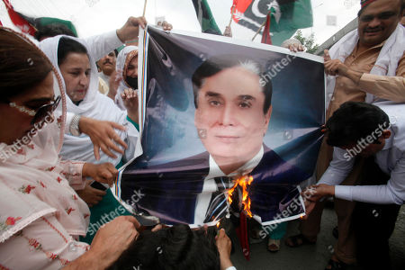 Supporters of Pakistan's People's party burn a picture of Javed Iqbal, Chairman of the National Accountability Bureau to protest the arrest of their leader Asif Ali Zardari, in Peshawar, Pakistan, . A Pakistani court has handed over the former president Zardari to a national anti-graft body for questions regarding a multi-million dollar money laundering case