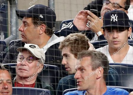 Singer/songwriter Paul Simon, lower left, with white cap, watches from the stands during the second baseball game of a doubleheader between the New York Yankees and the New York Mets, in New York