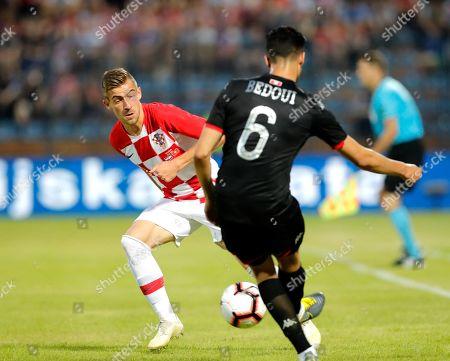 Stock Picture of Croatian  Dario Melnjak (L) in action against Tunisia's Rami Bedoui (R) during an International friendly soccer match between Croatia and Tunisia in Varazdin, Croatia, 11 June 2019.