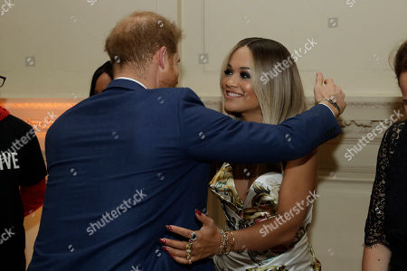 Britain's Prince Harry hugs singer Rita Ora during a reception before a concert hosted by his charity Sentebale at Hampton Court Palace, in London, . The concert will raise funds and awareness for Sentebale, the charity founded by Prince Harry and Lesotho's Prince Seeiso in 2006, to support children and young people affected by HIV and AIDS in Lesotho, Botswana and Malawi