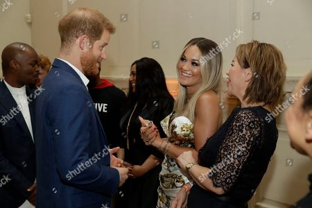 Britain's Prince Harry speaks to British singer Rita Ora and her mum Vera Sahatciu during a reception before a concert hosted by his charity Sentebale at Hampton Court Palace, in London, . The concert will raise funds and awareness for Sentebale, the charity founded by Prince Harry and Lesotho's Prince Seeiso in 2006, to support children and young people affected by HIV and AIDS in Lesotho, Botswana and Malawi