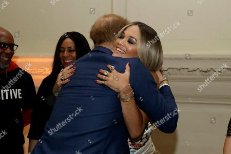 Britain's Prince Harry hugs British singer Rita Ora during a reception before a concert hosted by his charity Sentebale at Hampton Court Palace, in London, . The concert will raise funds and awareness for Sentebale, the charity founded by Prince Harry and Lesotho's Prince Seeiso in 2006, to support children and young people affected by HIV and AIDS in Lesotho, Botswana and Malawi