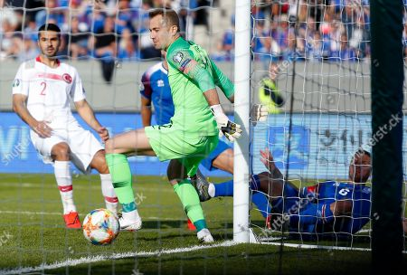 Iceland Turkey Euro 2020 Soccer. Iceland's Ragnar Sigurdsson, right, scores his first goal against Turkey's Mert Gunok, center, during the Euro 2020 group H qualifying soccer match between Iceland and the Turkey at Laugardalsvollur stadium in Reykjavik, Iceland