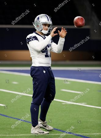 Dallas Cowboys long snapper Drew Scott reaches out for a ball as he participates in drills at the team's NFL football training facility in Frisco, Texas