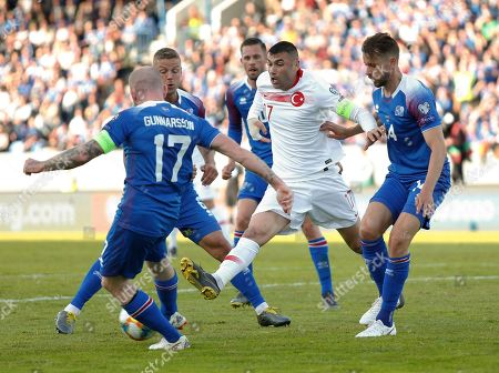 Iceland Turkey Euro 2020 Soccer. Iceland's Aron Einar Gunnarsson, left, is challenged by Turkey's Burak Yilmaz, center, during the Euro 2020 group H qualifying soccer match between Iceland and the Turkey at Laugardalsvollur stadium in Reykjavik, Iceland