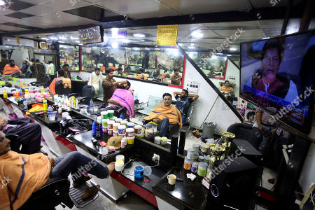 People at a barber shop watch a televised speech of Pakistan's Prime Minister Imran Khan, in Karachi, Pakistan, . Khan vowed to ensure that former President Asif Ali Zardari and ex-Premier Nawaz Sharif are held accountable for wrongdoing, accusing them of being responsible for the financial crisis currently faced by the Islamic nation