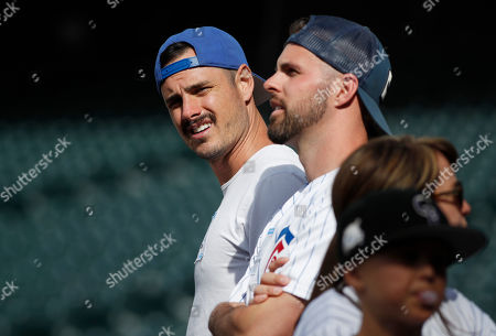 """Ben Higgins, Brandon Conley, r m. Ben Higgins, left, who appeared in the reality television show """"The Bachelor,"""" looks on with Brandon Conley, middle, as the two Cubs fans watch the team warm up before a baseball game against the Colorado Rockies, in Denver"""