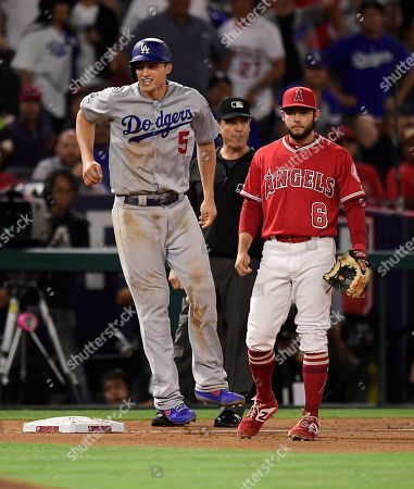 Corey Seager, David Fletcher. Los Angeles Dodgers' Corey Seager, left, winces after injuring himself while rounding third on a single by Alex Verdugo as Los Angeles Angels third baseman David Fletcher stands by during the ninth inning of a baseball game, in Anaheim, Calif
