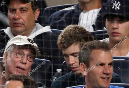 Singer/songwriter Paul Simon, lower left, watches from the stands during the second baseball game of a doubleheader between the New York Yankees and the New York Mets, in New York