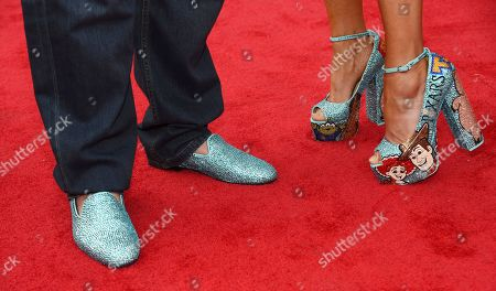 """Voice cast member John Ratzenberger, left, and his date show off their footwear at the premiere of the film """"Toy Story 4"""" at the El Capitan Theatre, in Los Angeles"""