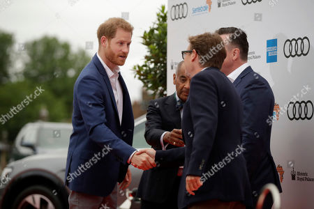 Prince Harry is greeted by the Managing Director of Audi UK Andrew Doyle, right obscured, and the Chairman of Sentebale Johnny Hornby, second right shaking hands