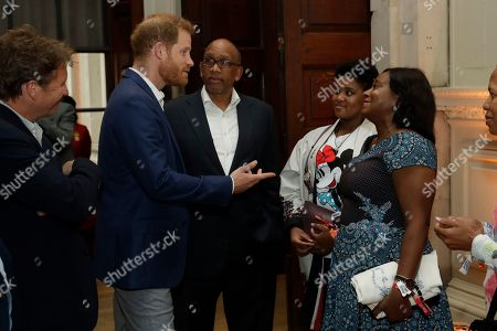 Stock Photo of Prince Harry speaks to Lesotho's Prince Seeiso, his wife Princess Mabereng Seeiso and daughter Princess Masentle Tabitha Seeiso during a reception
