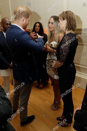 Prince Harry speaks to Rita Ora and her mum Vera Sahatciu during a reception