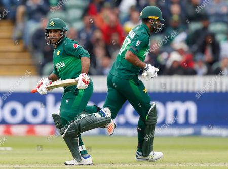 Pakistan's captain Sarfaraz Ahmed, left passes teammate Pakistan's Wahab Riaz as they take runs off the bowling of Australia's Nathan Coulter-Nile during the Cricket World Cup match between Australia and Pakistan at the County Ground in Taunton, south west England