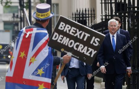 Britain's Conservative Party lawmaker Michael Fallon arrives passing a demonstrator, to attend the launch of Boris Johnson's leadership campaign, in London, . Boris Johnson solidified his front-runner status in the race to become Britain's next prime minister on Tuesday, gaining backing from leading pro-Brexit lawmakers