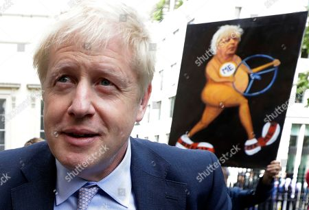 Britain's Conservative Party lawmaker Boris Johnson walks past a satirical art work held up by artist Kaya Mar as he arrives to launch his leadership campaign, in London, . Boris Johnson solidified his front-runner status in the race to become Britain's next prime minister on Tuesday, gaining backing from leading pro-Brexit lawmakers