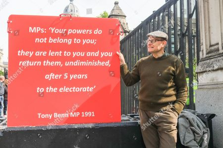A protester holds a sign with a quote by former MP Tony Benn outside Parliament