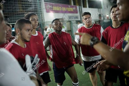 "Bigtboys transgender men's soccer player Bruno dos Santos, center, and his teammates listen to their coach during a game against the Alligaytors, a gay men's team in Rio de Janeiro, Brazil. ""Despite dozens of bills, only homophobic and transphobic discrimination remains without any kind of (legal sanction),"" Supreme Court Justice Alexandre de Moraes said during a session in February"