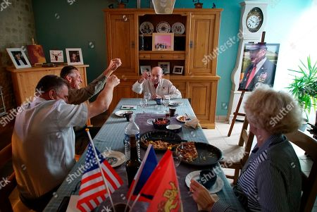 Christophe Coquel, left, Darrell Simpkins and Coquet's wife, Chantal, raise glasses of calvados brandy to toast D-Day veteran Ray Lambert at the Coquel home in Le Douet de Chouain, France, on . The North Carolina man has been a frequent honored guest at the former French soldier's Normandy home since they first met 15 years ago