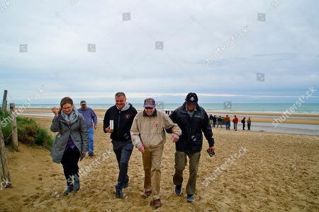 Former French Army officer Christophe Coquel, foreground second left, and Dr. Darrell Simpkins, foreground right, flank D-Day survivor Ray Lambert as they leave Omaha Beach in Colleville-sur-Mer, France, on . The 98-year-old North Carolina veteran returned to Normandy to mark the 75th anniversary of the Allied invasion