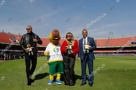Brazilian singer Leo Santana, left, and Colombian singer Karol G, second right, artists that will perform at the opening ceremony of the Copa America on Friday, pose for pictures with the tournament's mascot Zizito and Brazilian former soccer player Cafu, right, at the Morumbi stadium n Sao Paulo, Brazil, . The Copa America soccer tournament will run from June 14 until July 7 in Brazil