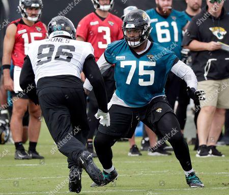 Jacksonville Jaguars offensive lineman Jawaan Taylor (75) blocks defensive lineman Datone Jones (96) during an NFL football practice, in Jacksonville, Fla