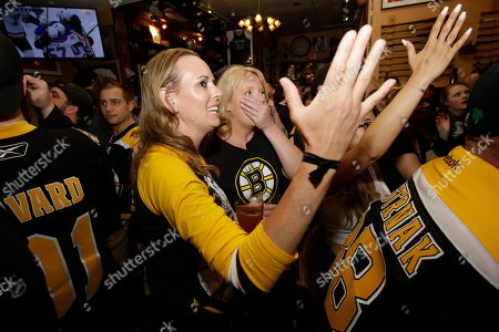Stock Photo of Boston Bruins fans Amy O'Connor, of Dudley, Mass., center left, and Jennifer Lynch, of Auburn, Mass., behind center, react as the St. Louis Blues score a goal against the Bruins during the first period of Game 7 of the NHL hockey Stanley Cup Final, while watching the game on TV in a bar, in Boston. The Blues beat the Bruins 4-1 to win the Stanley Cup