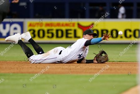 Miami Marlins shortstop Miguel Rojas tosses the ball to second baseman Starlin Castro to put out St. Louis Cardinals' Matt Carpenter at second for the first out of a double play hit into by Paul DeJong during the ninth inning of a baseball game, in Miami. The Marlins won 9-0