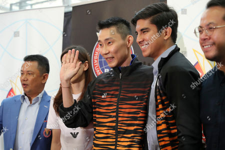 Malaysian badminton player Lee Chong Wei, center, waves to media after a press conference in Putrajaya, Malaysia, . Former World No. 1-ranked Lee has announced his retirement from badminton after 19 years following his battle with cancer