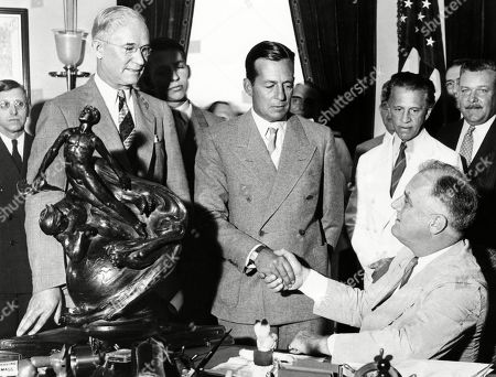 President Franklin Roosevelt shakes hands with Donald Douglas, the 1936 winner of the Collier Trophy. Douglass was awarded for the years outstanding contribution aviation, the Douglas twin engine commercial transport plane. Standing L-R: Charles Hoorner, Pres. Of National Aeronautics Association; Donald Douglas; George Creel. July 1, 1936.