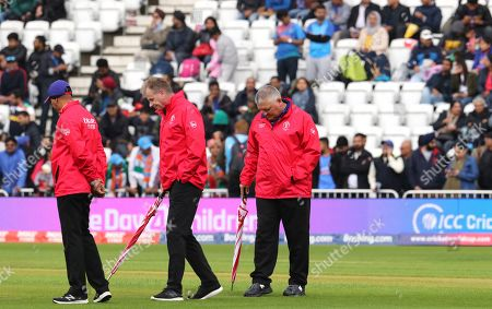 Umpires Paul Ronald Reiffel of Australia, middle, with Marais Erasmus of South Africa, right, inspection the ground as rain delays the start of the Cricket World Cup match between India and New Zealand at Trent Bridge in Nottingham