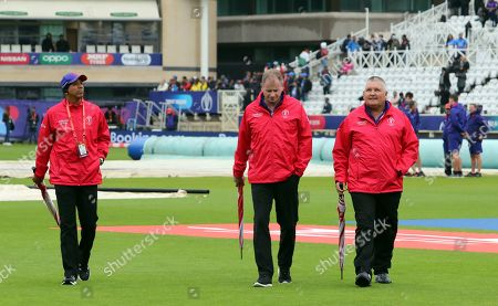 Umpires Joel Wilson of West Indies, left, with Paul Ronald Reiffel of Australia, middle, and Marais Erasmus of South Africa walk off the field after inspecting the ground as the rain delays start of the Cricket World Cup match between India and New Zealand at Trent Bridge in Nottingham