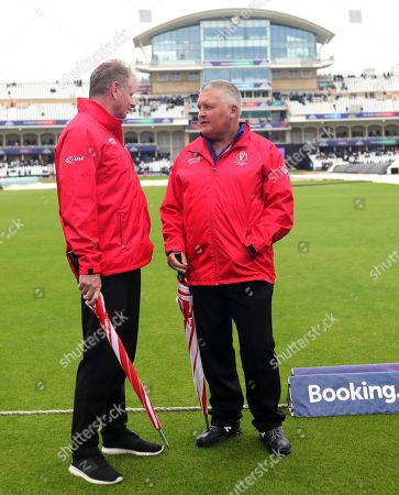 Umpires Paul Ronald Reiffel of Australia, left, with Marais Erasmus of South Africa walk off the field after inspecting the ground as the rain delays start of the Cricket World Cup match between India and New Zealand at Trent Bridge in Nottingham