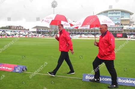 Umpires Paul Ronald Reiffel of Australia, left, with Marais Erasmus of South Africa walk off the field after calling off the the Cricket World Cup match between India and New Zealand at Trent Bridge in Nottingham, due to rain. Match abandoned without a ball bowled