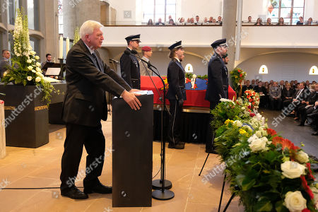 Stock Photo of Volker Bouffier (L), Governor of the state of Hesse, delivers the eulogy while standing next to the coffin of murdered German politician Walter Luebcke at Luebcke's memorial service at St. Martin church in Kassel, Germany, 13 June 2019. Luebcke was found dead, shot in the head at close range, on the terrace of his home on 02 June. Investigators have ruled out suicide and are investigating the case as murder. Luebcke, a Christian Democrat (CDU), was outspoken in his pro-immigration views, and one possibility investigators are pursuing is a right-wing motive to the shooting.