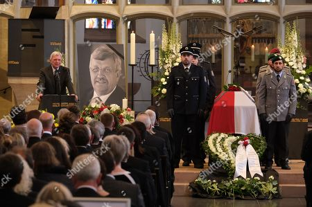 Volker Bouffier (L), Governor of the state of Hesse, delivers the eulogy while standing next to a portrait and the coffin of murdered German politician Walter Luebcke at Luebcke's memorial service at St. Martin church in Kassel, Germany, 13 June 2019. Luebcke was found dead, shot in the head at close range, on the terrace of his home on 02 June. Investigators have ruled out suicide and are investigating the case as murder. Luebcke, a Christian Democrat (CDU), was outspoken in his pro-immigration views, and one possibility investigators are pursuing is a right-wing motive to the shooting.