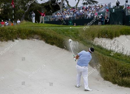 Kiradech Aphibarnrat of Thailand hits from a sand trap by the first green during the first round of the 119th US Open Championship at the Pebble Beach Golf Links in Pebble Beach, California, USA, 13 June 2019. The tournament will be played from 13 June to 16 June.