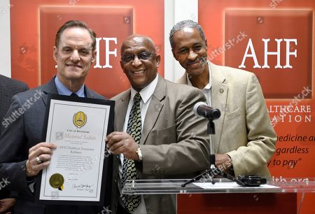 Stock Photo of Baltimore Mayor Jack Young, center, is joined by Baltimore City Councilman Robert Stokes, right, to present AHF President Michael Weinstein, left, with a special recognition during the grand opening of the AHF Baltimore Healthcare Center on in Baltimore