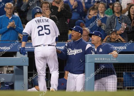 Los Angeles Dodgers manager Dave Roberts, center, and bench coach Bob Geren greet David Freese after Freese hit a two-run home run during the fifth inning of a baseball game against the Chicago Cubs in Los Angeles