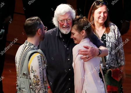 Stock Photo of Amanda Knox is hugged by Irishman Peter Pringle, as her fiancee Christopher Robinson, left, and mother Edda Mellas, right, look on during a Criminal Justice Festival at the University of Modena, Italy, Friday, June, 2019. Knox, a former American exchange student who became the focus of a sensational murder case, arrived in Italy Thursday for the first time since an appeals court acquitted her in 2011 in the slaying of her British roommate. Pringle had been sentenced to death in 1980 for the murder of two Irish police officers, this sentence was commuted to 40 years imprisonment of which he served 14 years and ten months until his conviction was quashed by the Court of Criminal Appeal in 1995