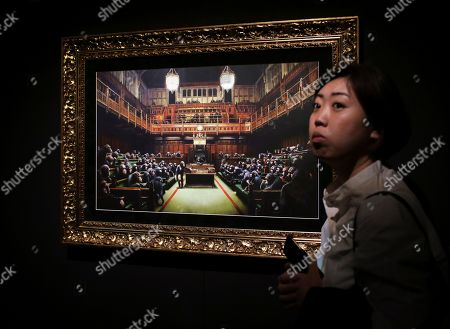 """A woman walks past a lithograph by British artist Banksy titled """"Monkey Parliament"""" at an exhibition in Lisbon . The exhibition 'BANKSY: Genius or Vandal' featuring 70 works by the artist opened Friday and runs until October 27"""