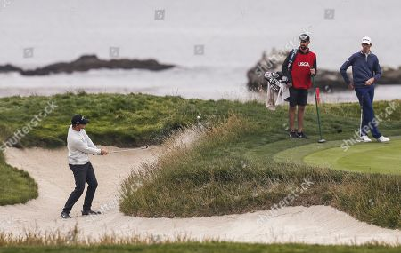 Chesson Hadley of the US (R) watches as Thomas Pieters of Belgium (L) hits from a sand trap bv the seventeenth green during the second round of the 119th US Open Championship at the Pebble Beach Golf Links in Pebble Beach, California, USA, 14 June 2019. The tournament is being played from 13 June to 16 June.