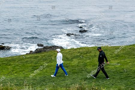 Tyrell Hatton of England (L) and Gary Woodland of the US (R) walks on the seventh hole next to the Pacific Ocean during the second round of the 119th US Open Championship at the Pebble Beach Golf Links in Pebble Beach, California, USA, 14 June 2019. The tournament is being played from 13 June to 16 June.